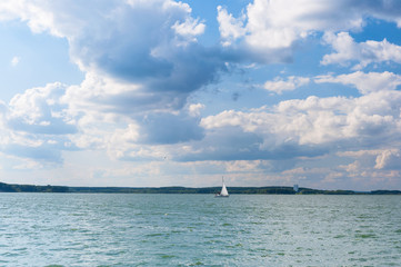 Lake under sky with clouds and sailboat