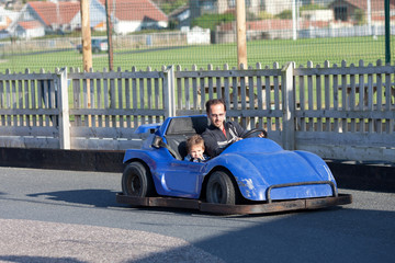 Father and child having fun on a go cart