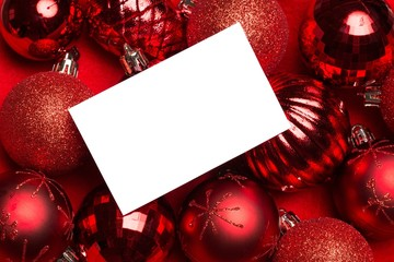 White page on red christmas baubles