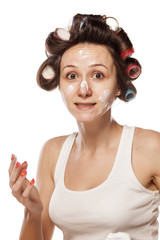 young woman with curlers and cream on her face