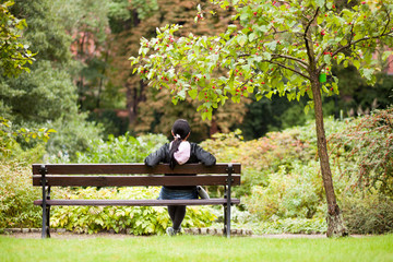 Girl sitting on a bench in a park