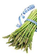 Fresh green asparagus and measuring tape.