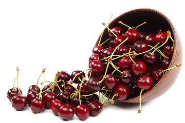 Fresh cherries in a wooden bowl on a white background.