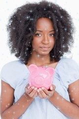 Composite image of young woman holding a pink piggy bank close