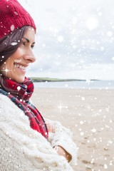 woman in knitted hat and pullover smiling at beach