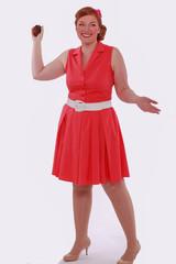 Frau im roten Kleid 60 Jahre Style , wirft mit einem Muffin