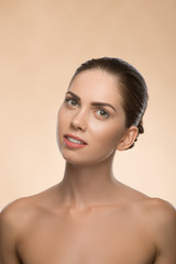 Young woman with beautiful healthy face - isolated on beige back