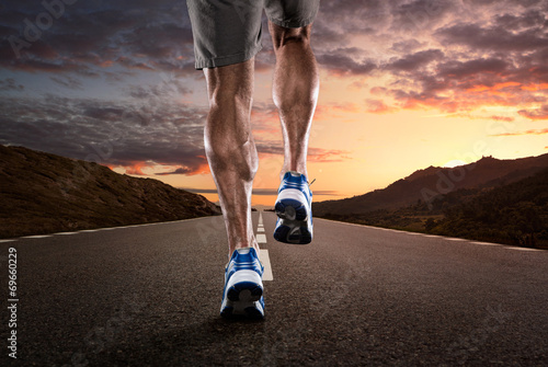 Close up of athlete running on the empty road - 69660229