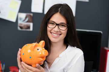 lächelnde schülerin hält sparschwein in der hand