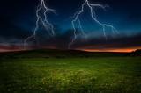 Fototapeta Thunderstorm with lightning in green meadow