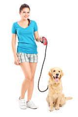 Full length portrait of a young girl walking a dog