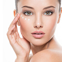woman with healthy face applying cosmetic cream under the eyes