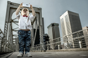 Boy with gadget on the bridge in the city of skyscrapers