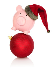 Piggy bank with Santa Claus hat balancing on a Christmas ball