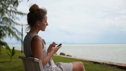 Woman Using Smart Phone at the Sea.
