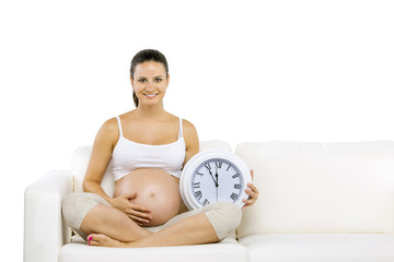Pregnant woman with wall clock