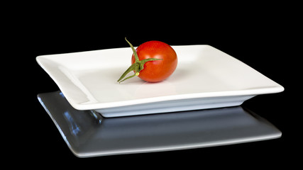 White plate with a red ripe tomato
