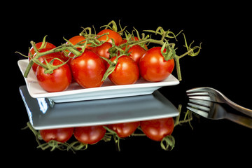 Red ripe tomatoes on a white plate with a fork