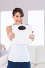 Fit brunette smiling at camera holding scales