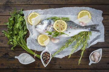 Pescado fresco con limón y hierbas en la cocina para la cena