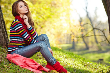 Fall woman relaxing happy in autumn forest foliage sitting