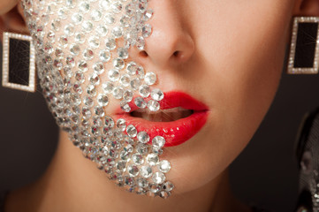 Beautiful girl with makeup with crystals on the face