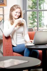frau mit laptop trinkt kaffe in einem cafe