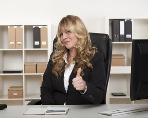 Attractive businesswoman giving a thumbs up
