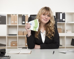 Successful businesswoman brandishing money
