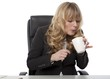 Businesswoman blowing on a mug of hot coffee