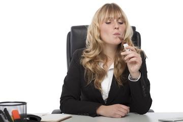 Businesswoman enjoying a chocolate bar at work