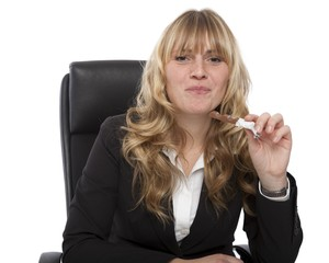 Businesswoman eating a candy at her desk
