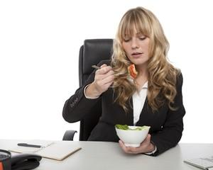 Businesswoman eating salad at her desk