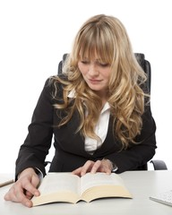 Young businesswoman sitting reading at her desk