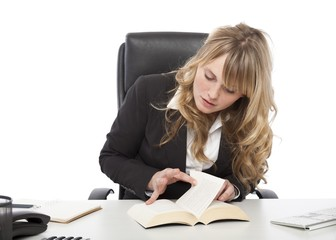 Young businesswoman paging through a book