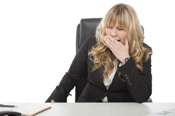 Bored young businesswoman yawning