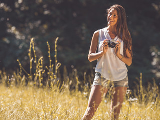 Attractive female relaxing in nature.Holding camera.