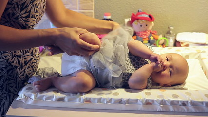 Mom getting her baby dressed