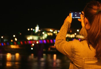 Young woman taking photo with cell phone