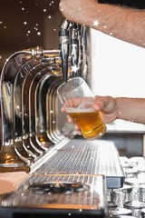 Composite image of bartender pulling a pint of beer