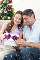 Composite image of loving couple opening christmas gift