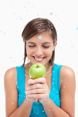 Smiling teenager looking at a green apple