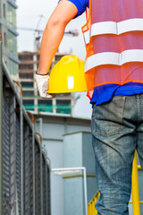 Worker on construction site with helmet or hard hat