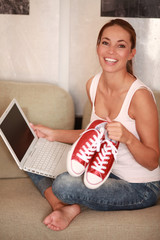 junge Frau auf Couch zeigt Ihre neuen Schuhe
