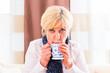 Seniorin trinkt Tee und kuriert ihre Grippe