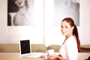 Frau mit Kaffeetasse am Laptop