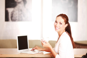 Frau mit Tasse am Laptop