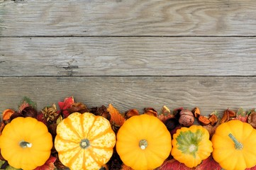 Autumn border of pumpkins and vegetables over a wood background