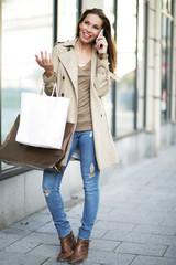 junge Frau telefoniert auf Einkaufstour