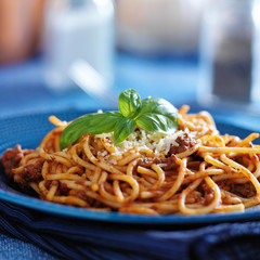 spaghetti in bolognese sauce on blue plate